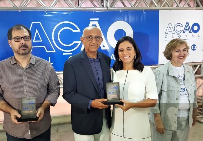 Servidora Lisiane Salomão recebe placa de homenagens da Ação Global.