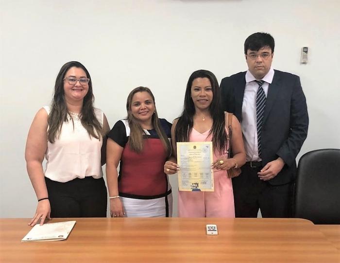 Juíza Urbanete de Angiolis ao lado da transgênero Mônica Costa, durante entrega da certidão.