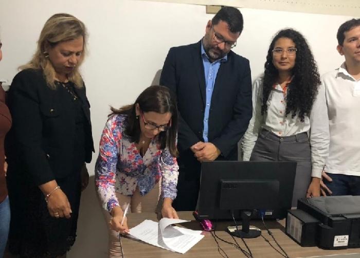 Juíza Nuza Maria observa Prefeita assinando convênio